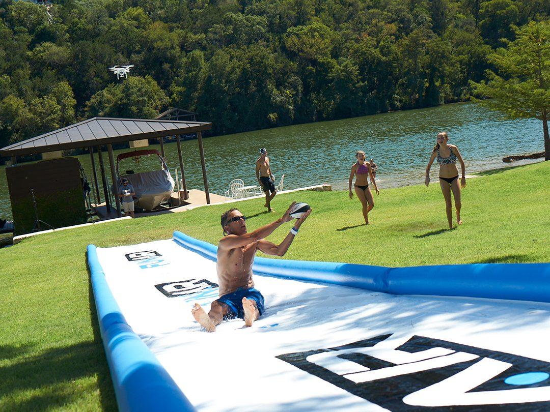 Person sliding backwards down a super slick lawn slide