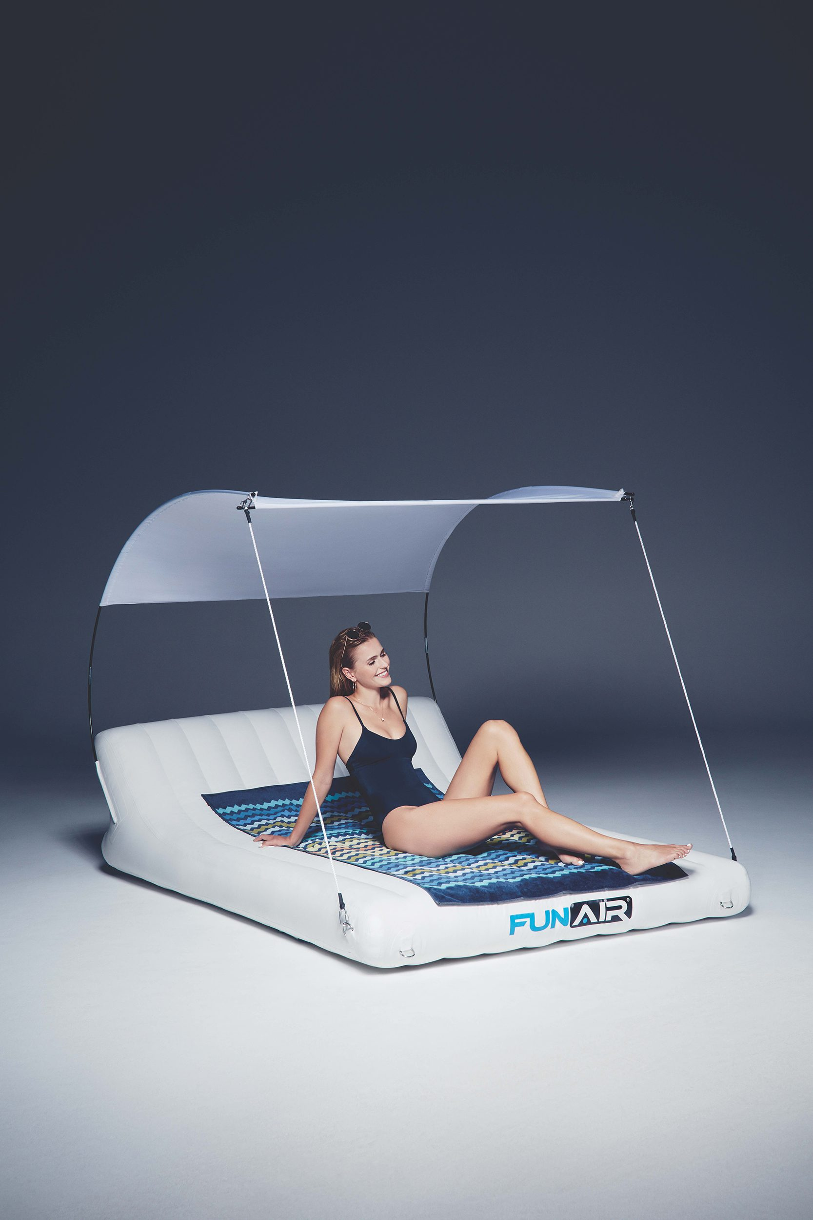 Woman using double shaded inflatable sun lounger
